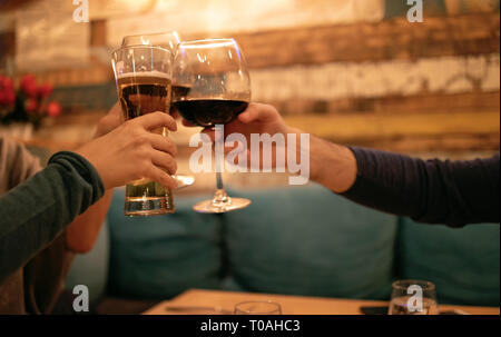 Friends in a restaurant toasting beer and wine. Three Friends in restaurant celebrating. Evening go out - Stock Image