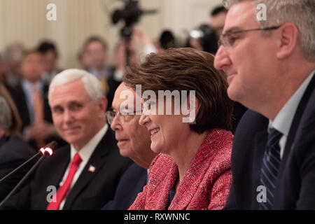 Marillyn Hewson, CEO of Lockheed Martin, center, speaks at the American Workforce Policy Advisory Board Meeting chaired by U.S President Donald Trump in the State Dining Room of the White House March 6, 2019 in Washington, DC. Vice President Mike Pence, left, and Commerce Secretary Wilbur Ross sit next to Hewson. - Stock Image