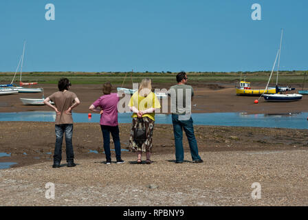 Four people standing on a shingle beach looking out over the tidal creeks  at Brancaster Staithe, North Norfolk, UK - Stock Image