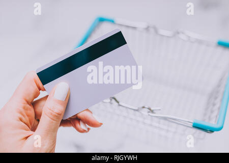 woman's hand holding payment card and empty shopping basket, concept of shopping and expenses - Stock Image