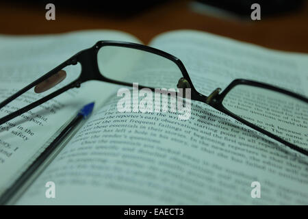 Reading glasses on an open book - Stock Image