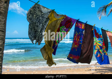 Colourful beach towels hanging from a tree on Bathsheba beach; Barbados - Stock Image