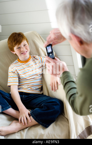 Senior man taking picture of smiling boy with camera phone - Stock Image