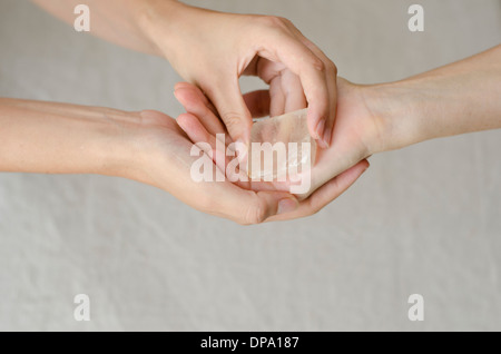 Womans hands giving a quartz crystal in healing gesture, with copy space room for text - Stock Image