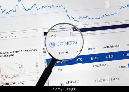 MONTREAL, CANADA - APRIL 26, 2019: Coinegg cryptocurrency digital assets exchange logo and home page on a laptop screen under magnifying glass. - Stock Image