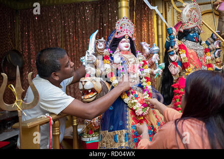 Two devout Hindu worshippers decorate a statue of the goddess Durga with flowers. In Ozone Park, Queens, New York. - Stock Image