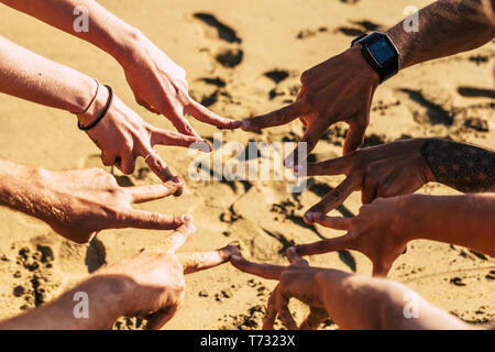 Four couples of hands. Caucasian happy couple enjoy the summer holiday vacation at the beach with coast cliff and blue sky. - Stock Image