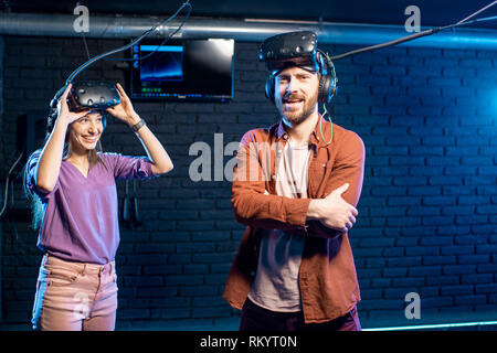 Happy man winning virtual reality game standing with young woman in the playing room - Stock Image