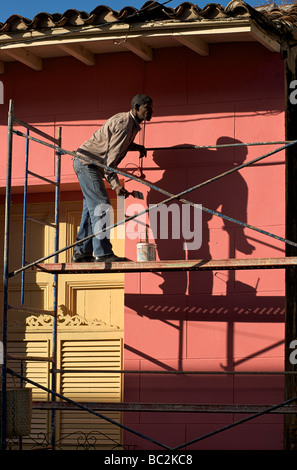 Cuban colonial house receiving a colourful coat of paint. Trinidad, Cuba. Trinidad, is a UNESCO World Heritage site. - Stock Image
