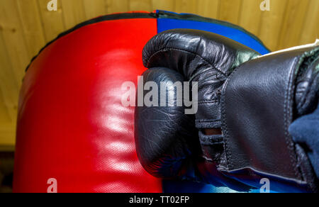 Closeup of a hand in a black padded boxing glove hitting a punch bag. No people in shot. - Stock Image