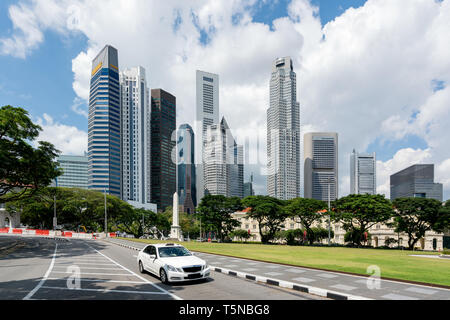 Taxi cab driving in road in Singapore downtown with Singapore skyscrapers building in background. Asia. - Stock Image