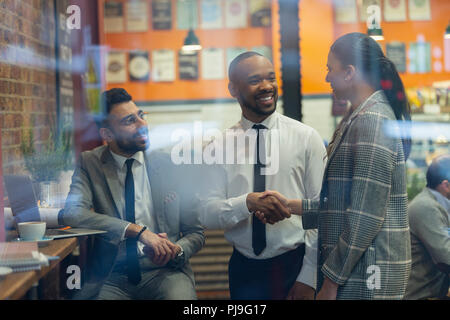 Smiling business people handshaking in cafe - Stock Image