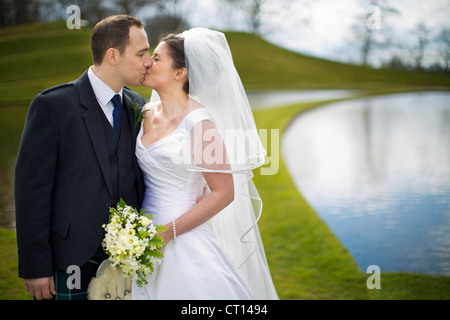 Newlywed couple kissing outdoors - Stock Image