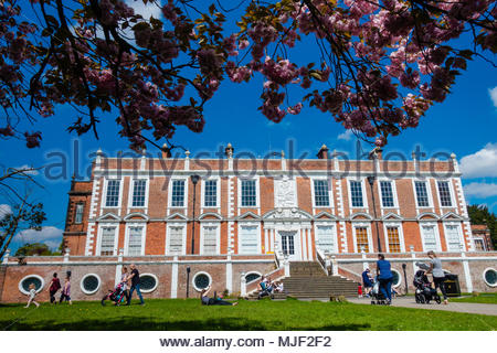 Croxteth Hall, Liverpool, UK 5 May 2018. UK Weather Croxteth Hall, Liverpool England UK 05/05 2018 People enjoying walking their children at Croxteth Hall in the Spring sunshine on the Bank Holiday Mayday Weekend at Croxteth Hall, View of Croxteth Hall from underneath a Spring blooming blossom tree Croxteth Country Park, Liverpool England UK Parts of Peaky Blinders were filmed here. Credit: Christopher Canty Photography/Alamy Live News - Stock Image