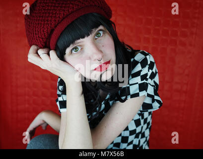Cool young woman against red background - Stock Image