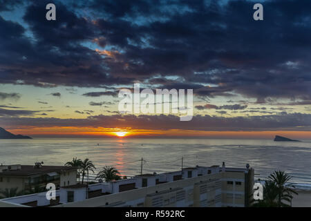 Benidorm, Costa Blanca, Spain, 30th November 2018. Sunrise over the bay in front of Poniente Beach with forecasts of temperatures set to reach the mid 20's Celsius today. Average temperatures over 17 degrees Celsius through the winter months make the Costa Blanca an ideal destination for cold and wet Brits. The sun rising above Poniente Beach. Credit: Mick Flynn/Alamy Live News - Stock Image