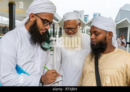 Bangladeshi Muslim Visiting the Masjid Negara (National Mosque) in Kuala Lumpur, Malaysia, Writing Email Address for Photographer. - Stock Image