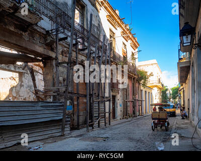 Dilapidated buildings and tricycle in the centre of Havana, capital of the island state of Cuba - Stock Image