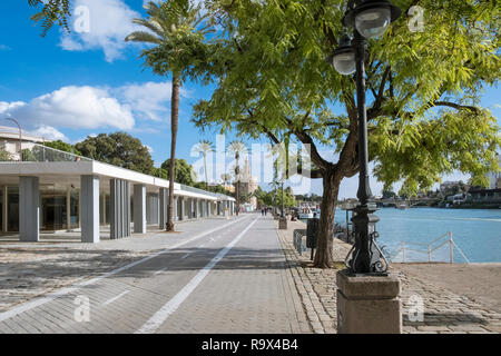 Walking path alongside the Guadalquivir river, with historic defensive tower Torre Del Oro in the distance, Seville, Spain. - Stock Image