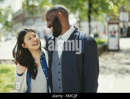 Affectionate couple laughing in sunny urban park - Stock Image