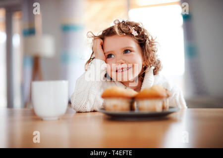 A portrait of happy small girl with muffins sitting at the table at home. - Stock Image