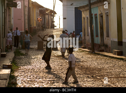 Late afternoon street scene in Trinidad, Cuba. Children playing with a ball in the street - Stock Image