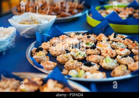 Bite sized snacks on large silver trays, appetizers or hors d'oeuvre at the buffet bar or self-service  restaurant as a starter, tapas or nibbles - Stock Image