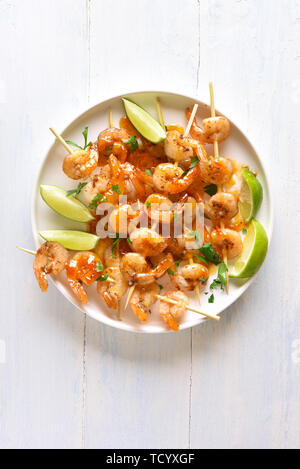 Tasty prawns skewers with greens, spices, lime and sauce on white plate over wooden table. Grilled shrimp skewers. Tasty seafood. Top view, flat lay. - Stock Image