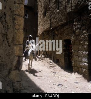 Boys riding a donkey Amran Yemen - Stock Image