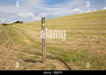 Public footpath in Cornwall across open field near the headland above Polkerris - Stock Image