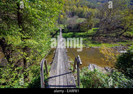 Small rope bridge over mountain river. Connection with the world. Tube rope is right mailbox. - Stock Image