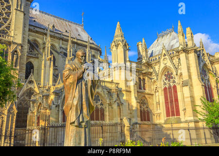 Details of Pope John Paul II statue on side of church Notre Dame of Paris, France. Gothic architecture of Cathedral of Paris, Ile de la cite. Beautiful sunny day in the blue sky. - Stock Image