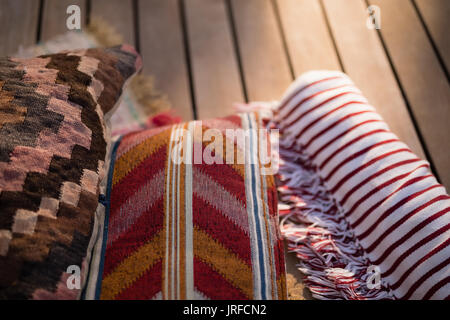 Cushions and picnic blanket on wooden plank - Stock Image