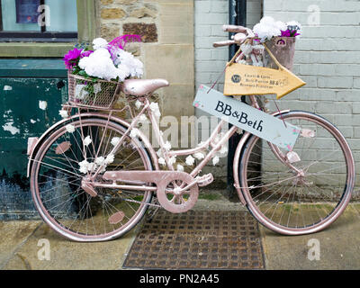 A ladies bicycle painted pink and decorated with flowers advertising BB and Beth a furniture restorers shop in Richmond North Yorkshire - Stock Image