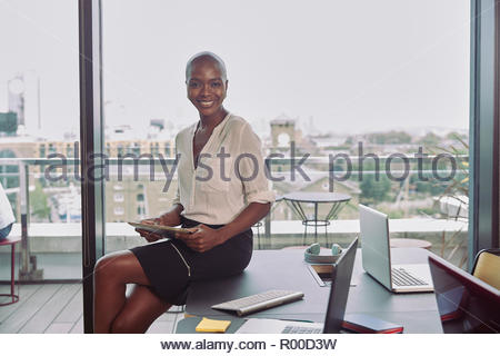 Young businesswoman holding digital tablet in conference room - Stock Image