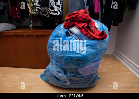 Someone has cleaned out their closet and made a bag of clothes to donate or purge - Stock Image