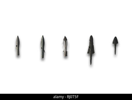 Five primitive bronze arrowheads. Isolated over white background - Stock Image