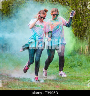 Two women runners, one holding a smart phone, being covered in paint on Macmillan cancer charity 5K color fun run. - Stock Image