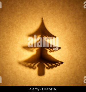 Backlit silhouette of Christmas tree shape cut out against brown tone paper, with spot highlight. - Stock Image