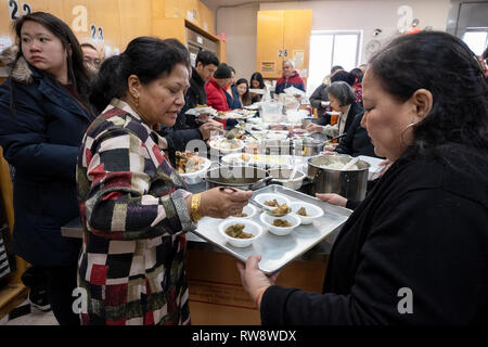 After feeding their monks several trays of food, a Buddhist congregation eats the remainder. In Elmhurst, Queens, New York City. - Stock Image