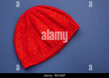 Red knitted woollen beanie hat on a blue background. - Stock Image