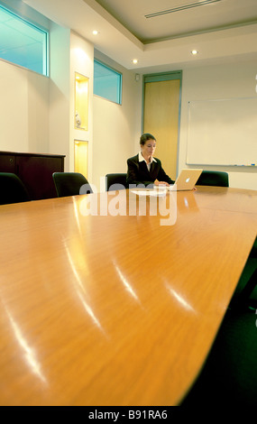 Business woman in boardroom with laptop - Stock Image