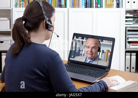 Woman with headset and book at her desk in front of her laptop having an online chat with her prof, text space - Stock Image