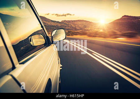 Road trip on sunset, car on the highway, conceptual image of escape and adventure travel, slow motion photo - Stock Image