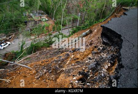 Collapsed electric poles, power lines, and damaged homes litter the Barrio Espino neighborhood after a landslide - Stock Image