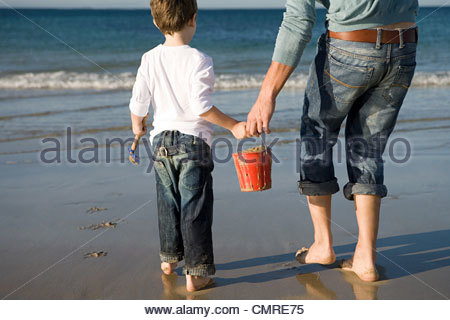 Father and son with bucket of sand - Stock Image