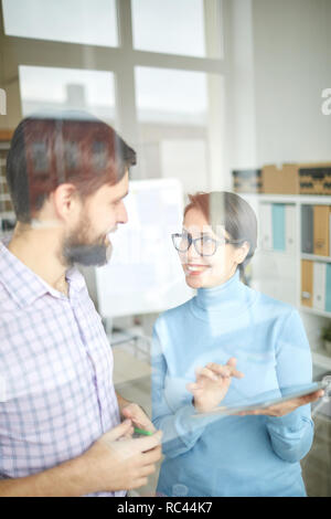 Cheerful businesswoman with tablet showing her colleague and explaining online financial data at working meeting - Stock Image