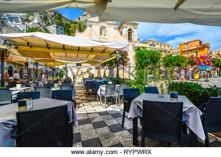 Afternoon lunch on Piazza Aprile on the Mediterranean island of Sicily in Taormina, Italy on a warm summer day with a church and mountains behind - Stock Image