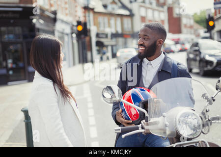 Smiling young businessman on motor scooter talking to friend on urban street - Stock Image