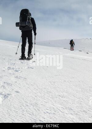 two men with heavy backpacks snowshoeing in winter mountain landscape. Huldraheimen, Gausdal Westfjel, Norway - Stock Image